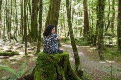 Muchacha que se sienta en el medio de un bosque foto de archivo libre de regalías