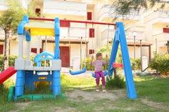 Muchacha que se sienta en el oscilación en el patio Fotos de archivo libres de regalías