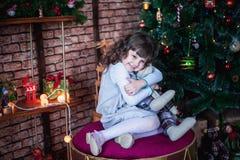 Muchacha que se sienta en el otomano delante del árbol y que abraza el conejito del juguete imagen de archivo libre de regalías