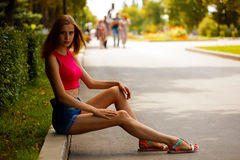 Muchacha que se sienta en el parque con el borde del camino en el encintado Fotos de archivo