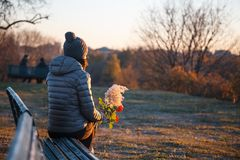 Muchacha que se sienta en el parque que considera el horizonte la puesta del sol con flujo Foto de archivo libre de regalías