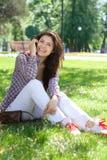 Muchacha que se sienta en el parque en la hierba y que habla en el teléfono Foto de archivo libre de regalías