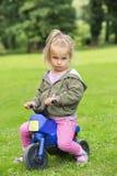 Muchacha que se sienta en el parque en una moto foto de archivo