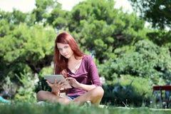 Muchacha que se sienta en el parque que estudia con la tableta Fotos de archivo