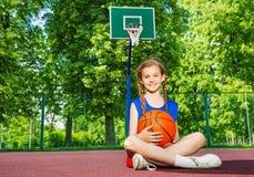 Muchacha que se sienta en el patio con la bola Fotografía de archivo libre de regalías