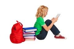 Muchacha que se sienta en el piso cerca de los libros y de la tableta de la tenencia del bolso Foto de archivo libre de regalías
