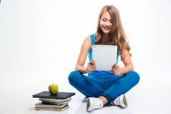 Muchacha que se sienta en el piso con cálculo de la tableta Imagenes de archivo