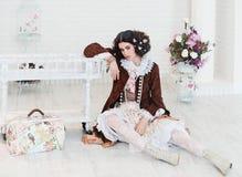 Muchacha que se sienta en el piso con el bolso Fotografía de archivo libre de regalías