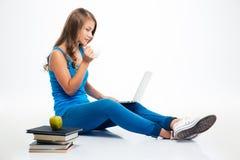 Muchacha que se sienta en el piso con el ordenador portátil y el café de consumición Imagen de archivo