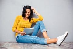 Muchacha que se sienta en el piso con la tableta Imágenes de archivo libres de regalías
