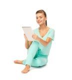 Muchacha que se sienta en el piso con PC de la tableta Foto de archivo libre de regalías
