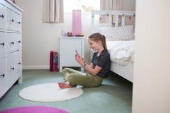 Muchacha que se sienta en el piso del dormitorio usando el teléfono móvil Fotografía de archivo