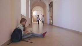 Muchacha que se sienta en el piso, libro de lectura y preparándose a la lección metrajes