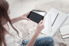 Muchacha que se sienta en el piso y que sostiene su teléfono Fotografía de archivo libre de regalías