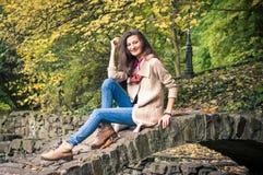 Muchacha que se sienta en el puente de piedra Imágenes de archivo libres de regalías