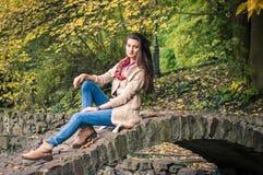 Muchacha que se sienta en el puente de piedra Foto de archivo