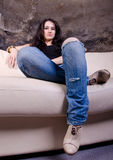 Muchacha que se sienta en el sofá Fotografía de archivo libre de regalías