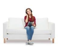 Muchacha que se sienta en el sofá con los auriculares y PC de la tableta Imágenes de archivo libres de regalías