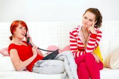Muchacha que se sienta en el sofá mientras que su teléfono de la novia Imagenes de archivo