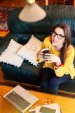 Muchacha que se sienta en el sofá que bebe una taza de té Fotos de archivo