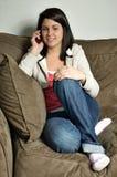 Muchacha que se sienta en el sofá que habla en el teléfono celular Imagenes de archivo