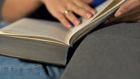 Muchacha que se sienta en el sofá y el libro de lectura almacen de video