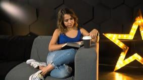 Muchacha que se sienta en el sofá y el libro de lectura almacen de metraje de vídeo