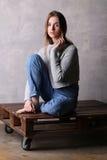 Muchacha que se sienta en el suéter que presenta en una cubierta Fondo gris Imágenes de archivo libres de regalías
