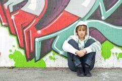 Muchacha que se sienta en el suelo cerca de la pared de la pintada Imagen de archivo libre de regalías