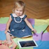 Muchacha que se sienta en el suelo con el ordenador de la tablilla Fotos de archivo libres de regalías