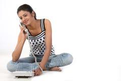 Muchacha que se sienta en el suelo que habla sobre el teléfono Fotos de archivo libres de regalías