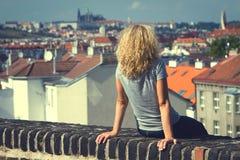 Muchacha que se sienta en el tejado de una casa Foto de archivo libre de regalías