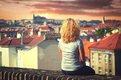 Muchacha que se sienta en el tejado de una casa Fotos de archivo libres de regalías