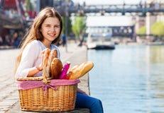 Muchacha que se sienta en el terraplén con la cesta de la comida campestre fotografía de archivo libre de regalías