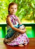 Muchacha que se sienta en el vector de madera Foto de archivo libre de regalías