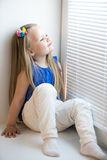 Muchacha que se sienta en el windowsill Foto de archivo