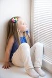 Muchacha que se sienta en el windowsill Fotos de archivo