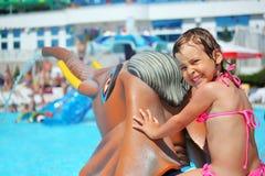 Muchacha que se sienta en elefante del juguete cerca de piscina Fotos de archivo