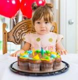 Muchacha que se sienta en Front Of Birthday Cake imagenes de archivo