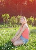 Muchacha que se sienta en hierba Fotos de archivo
