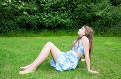Muchacha que se sienta en hierba Fotos de archivo libres de regalías