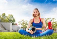 Muchacha que se sienta en hierba con la botella y la estera de la yoga Imagen de archivo