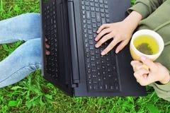 Muchacha que se sienta en hierba con la taza de té y de ordenador portátil Fotos de archivo