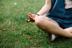 Muchacha que se sienta en hierba con las piernas cruzadas en cuadrado de ciudad Fotografía de archivo libre de regalías