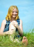 Muchacha que se sienta en hierba de prado Foto de archivo libre de regalías