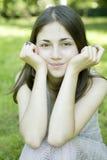 Muchacha que se sienta en hierba en parque Imagen de archivo