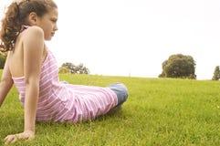 Muchacha que se sienta en hierba en parque. Imagen de archivo libre de regalías