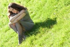 Muchacha que se sienta en hierba verde Imágenes de archivo libres de regalías