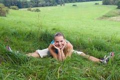 Muchacha que se sienta en hierba verde en el prado Fotos de archivo