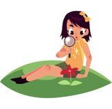 Muchacha que se sienta en hierba y que estudia la flor a través de la lupa Foto de archivo